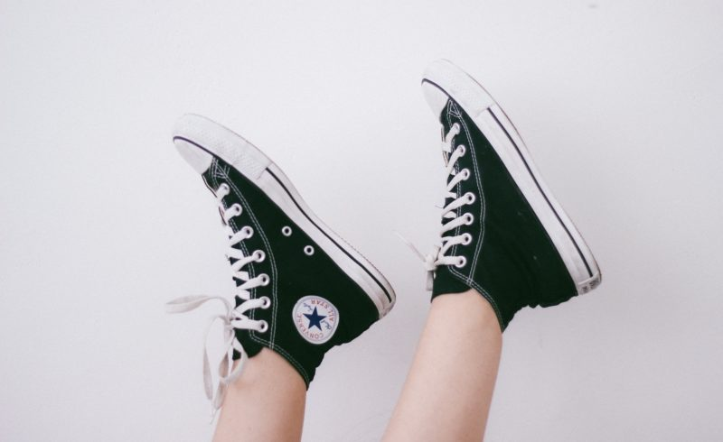 Pair of black high-top converse on raised feet