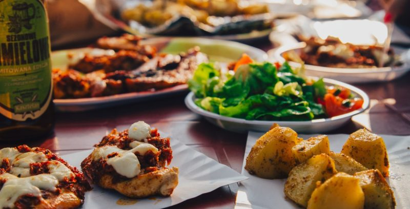 Several dishes on the table such as roasted potatoes, salads and pizza