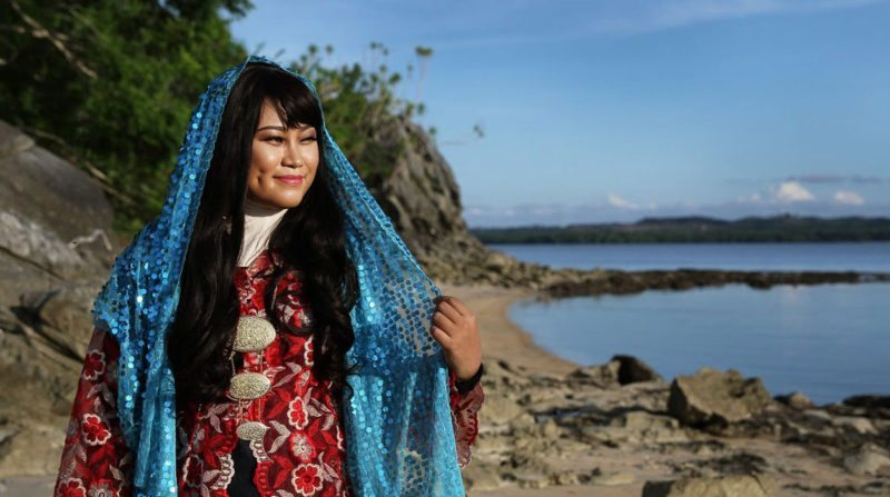 Woman in traditional costumes as she looks out into the sea for a musical at Sabah Fest