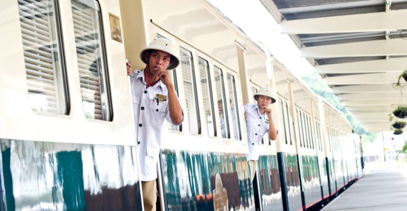 Two train guides blowing the whistle to announce the arrival or departure of the North Borneo Railway.