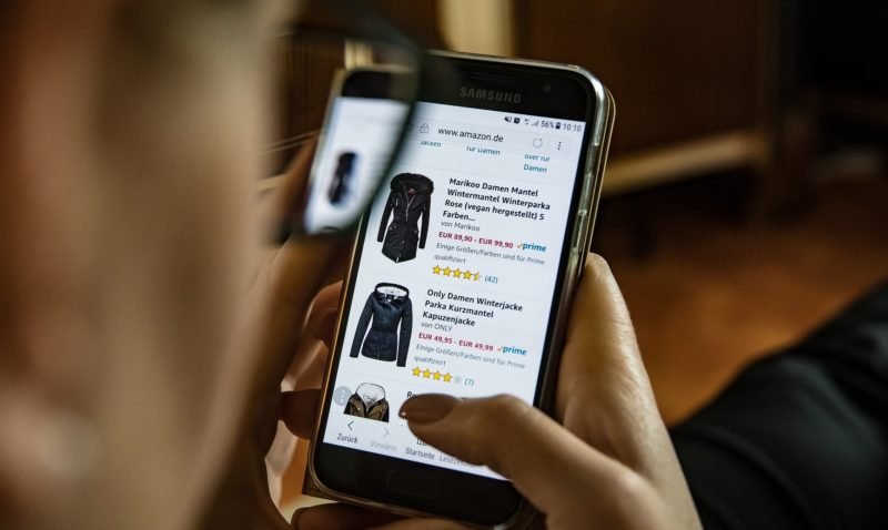 Person shopping on their mobile looking at coats