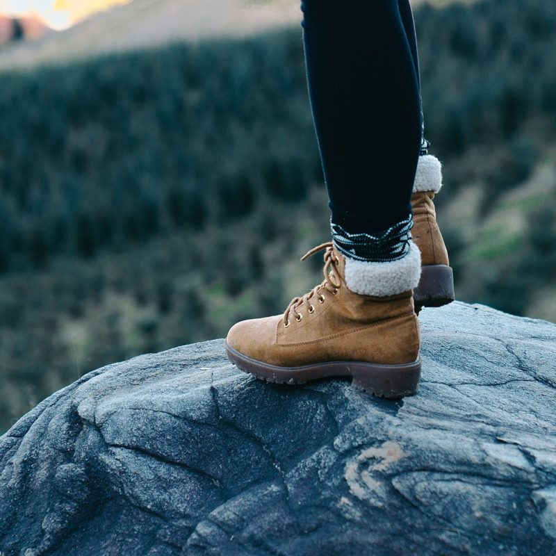 standing on winter boots on rock