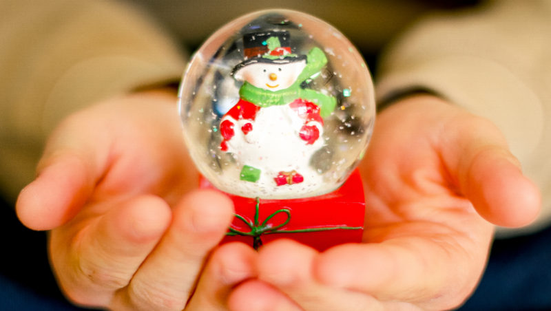 Snowglobe with a snowman insted on the palms of someones's hands
