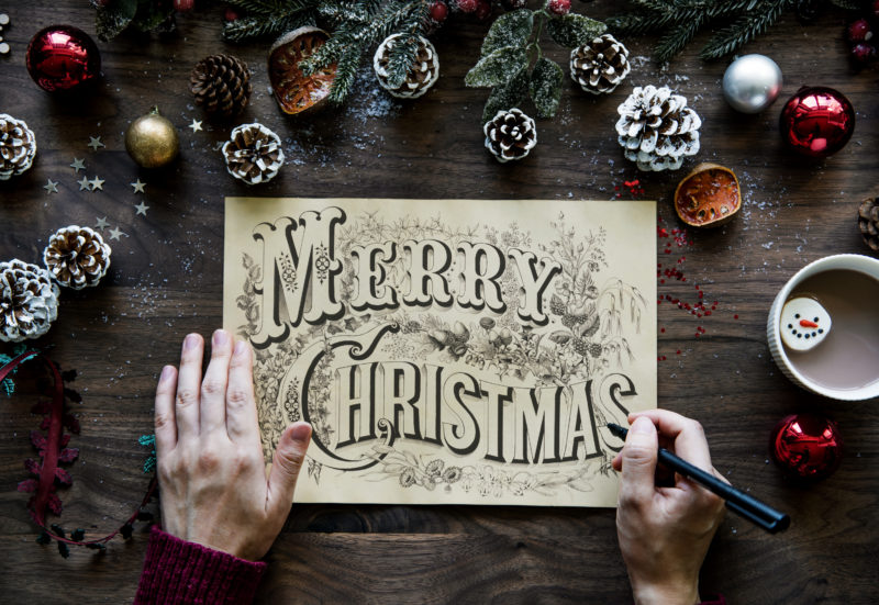 Merry Christmas drawn on the card at a wooden table with Christmas decor