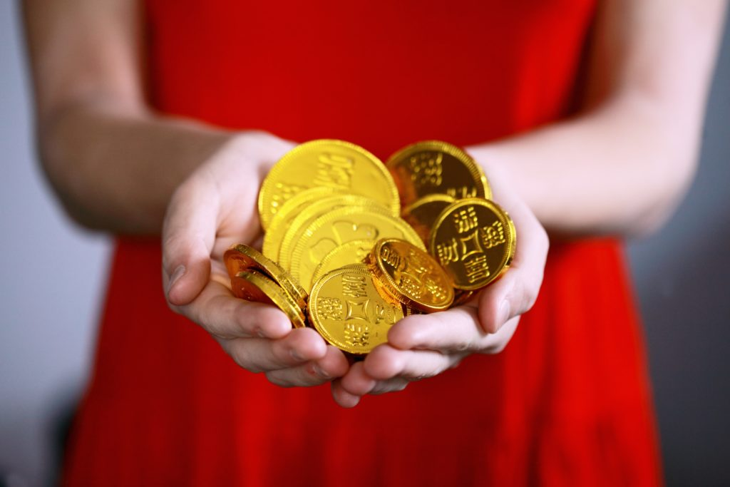 woman holding golden chinese coins