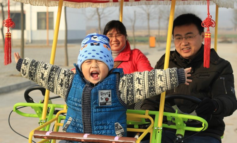 Chinese family of three taking a ride with the kid in front