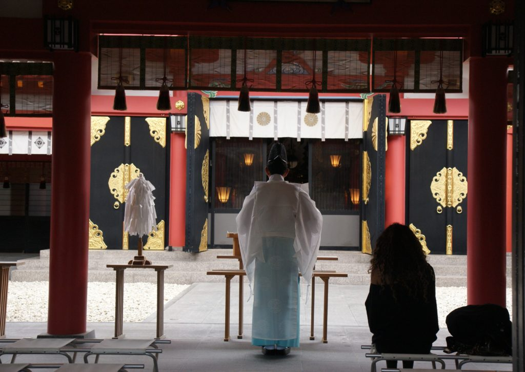 Prayers at a shrine with priest back facing us