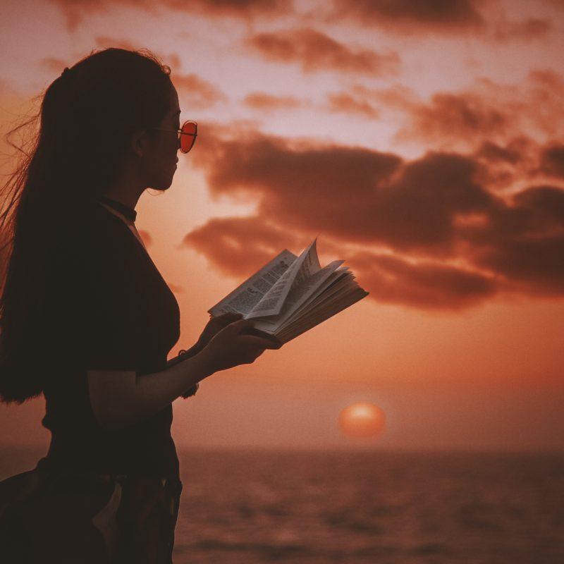 girl reading book sunset
