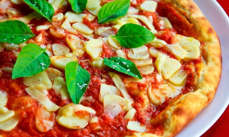 Pizza with garlic, tomato sauce and basil leaves