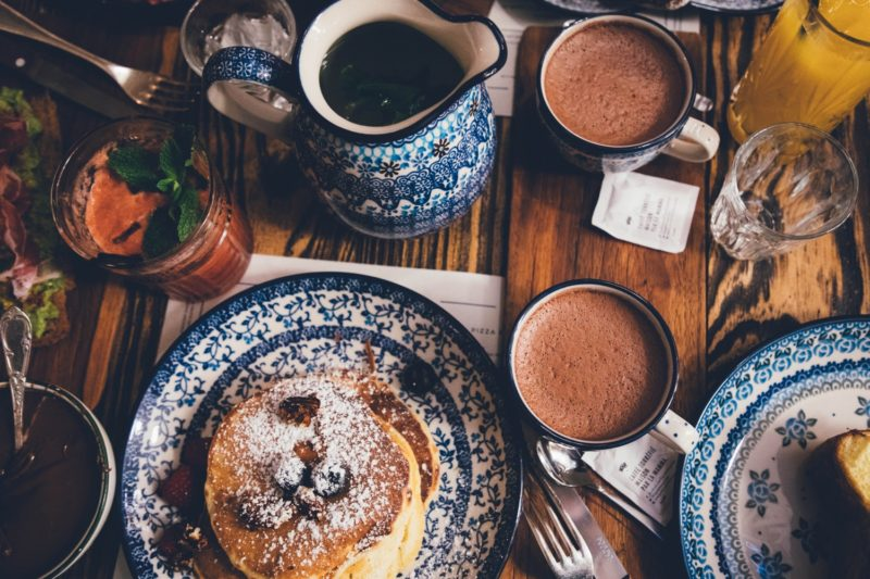 Dining table with hot drinks and pancakes