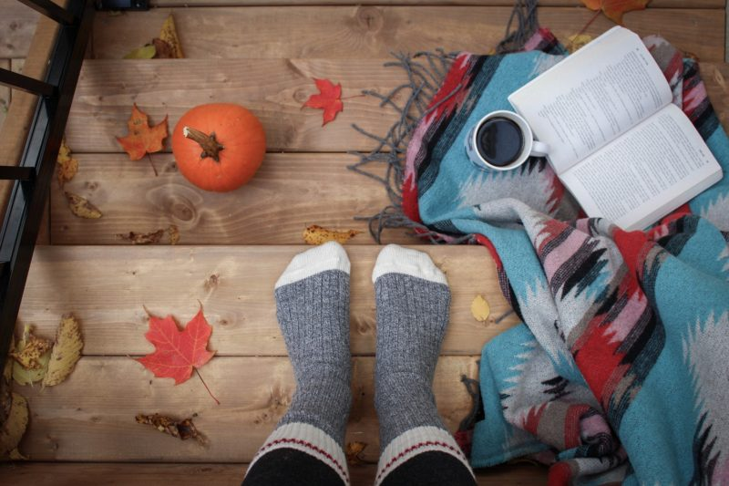 Person with socks, coffee and book with blanket at autumn