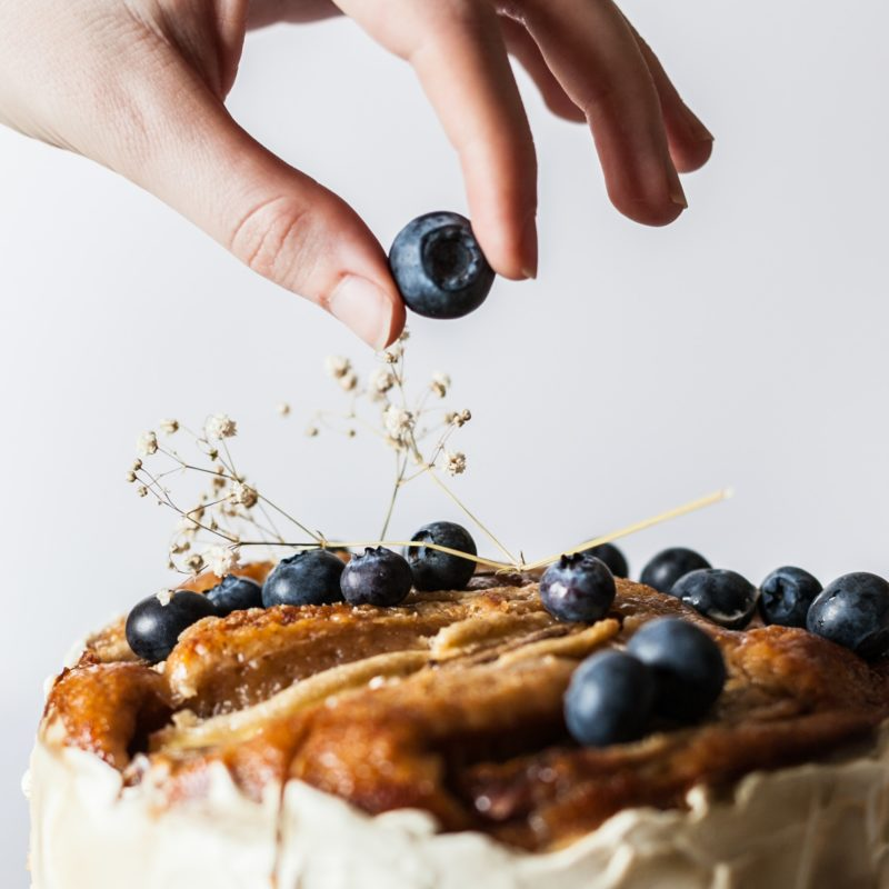 hand placing a blueberry on cake baking