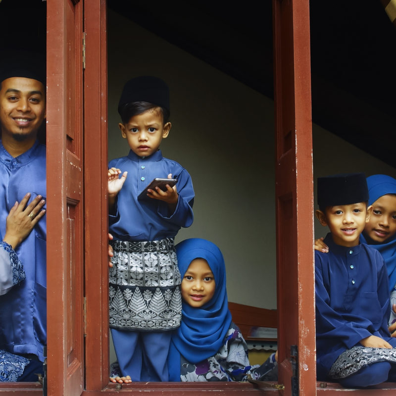 family in blue baju raya clothes