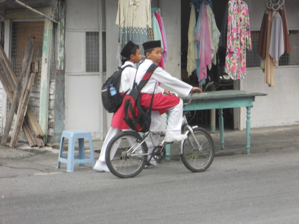 2 boys on bike riding in Kampung