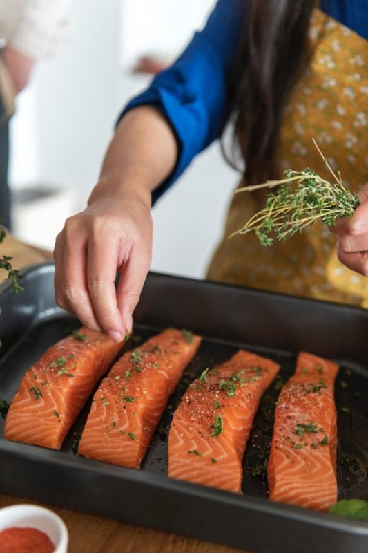 chef prepping salmon herbs