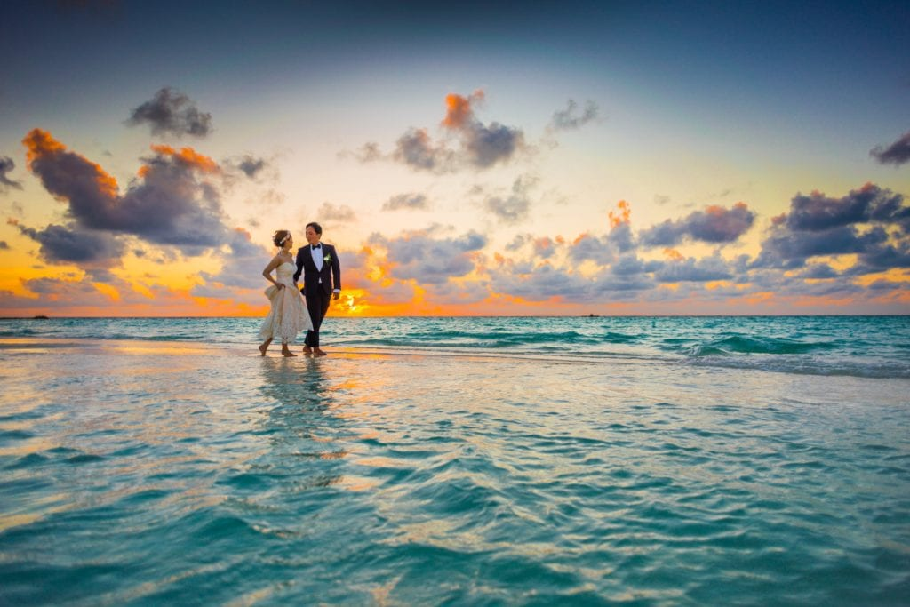 couple walking by the seaside with sunset skies