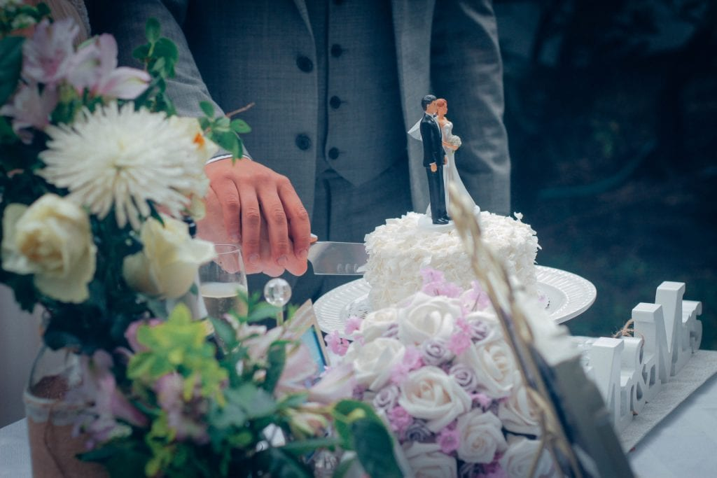 cake cutting ceremony of white wedding cake with flowers at bottom