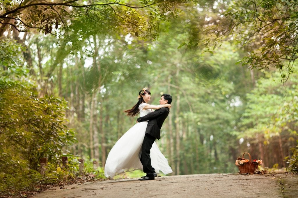 wedding couple hugging with trees in background