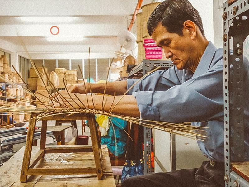 a weaver in action using rattan to craft products