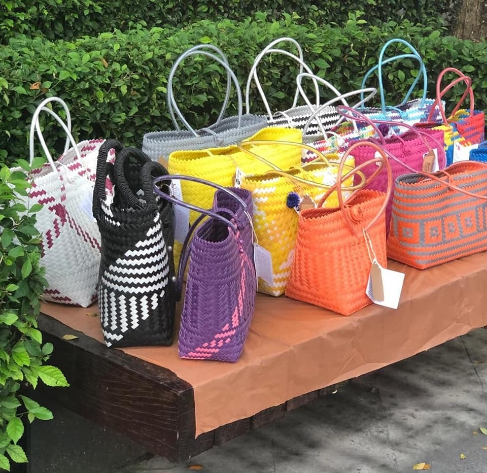 Colourful hand woven bags on bench display