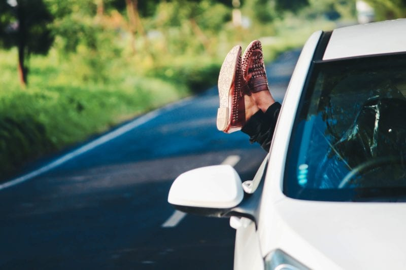 road trip foot sticking out of car