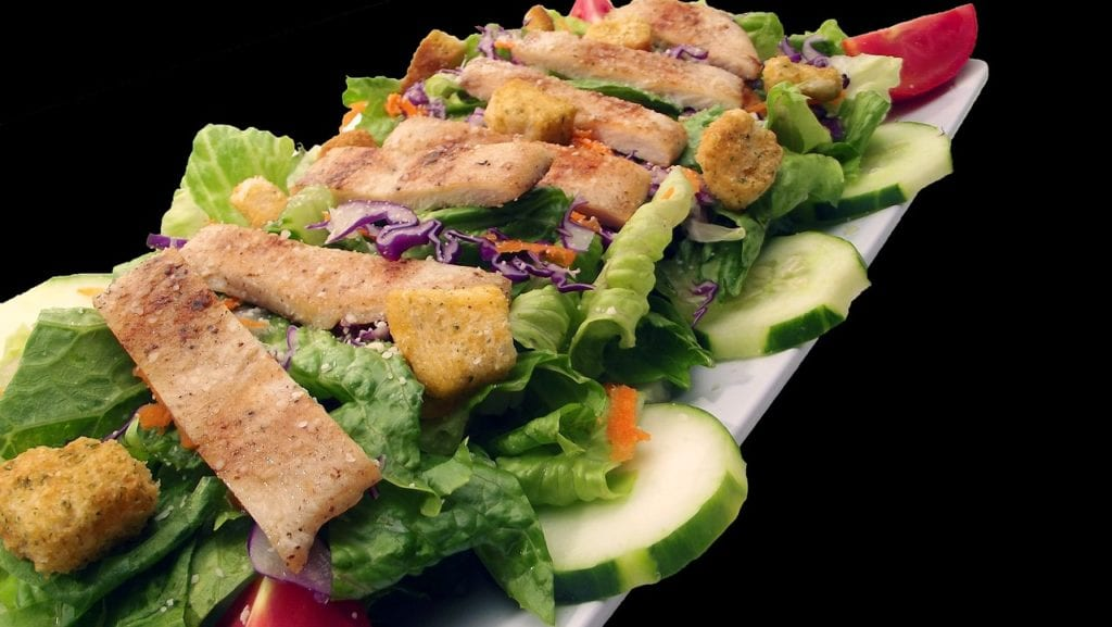 salad with grilled chicken on black background