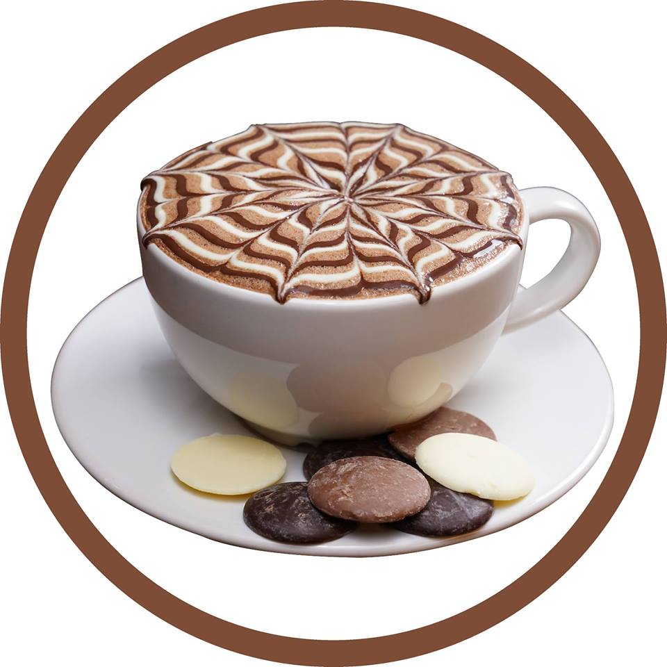 hot chocolate in white cup with cookies on plate