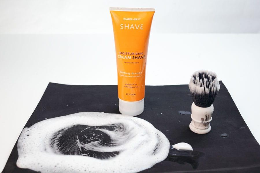 Shaving foam in orange tube on black surface with foam spread out