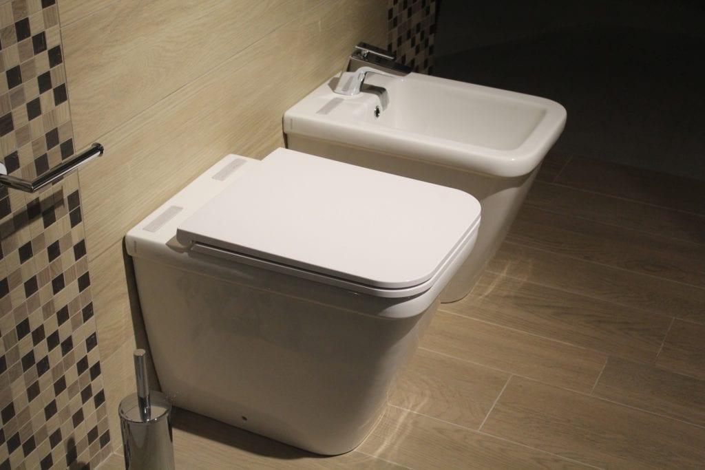 Toilets and bidet on brown panel floor
