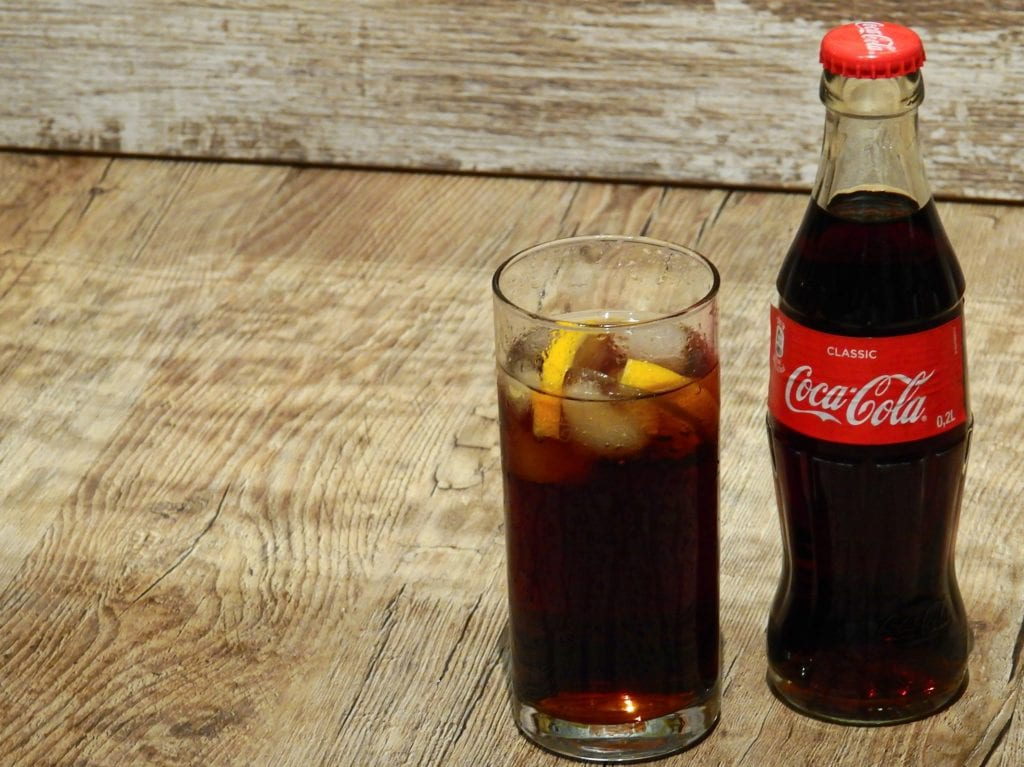 Bottle of Coke with glass on side