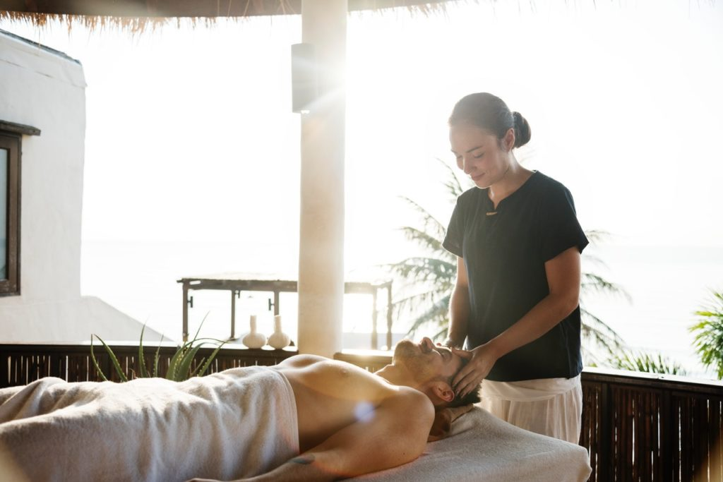 man enjoying spa massage by female masseur