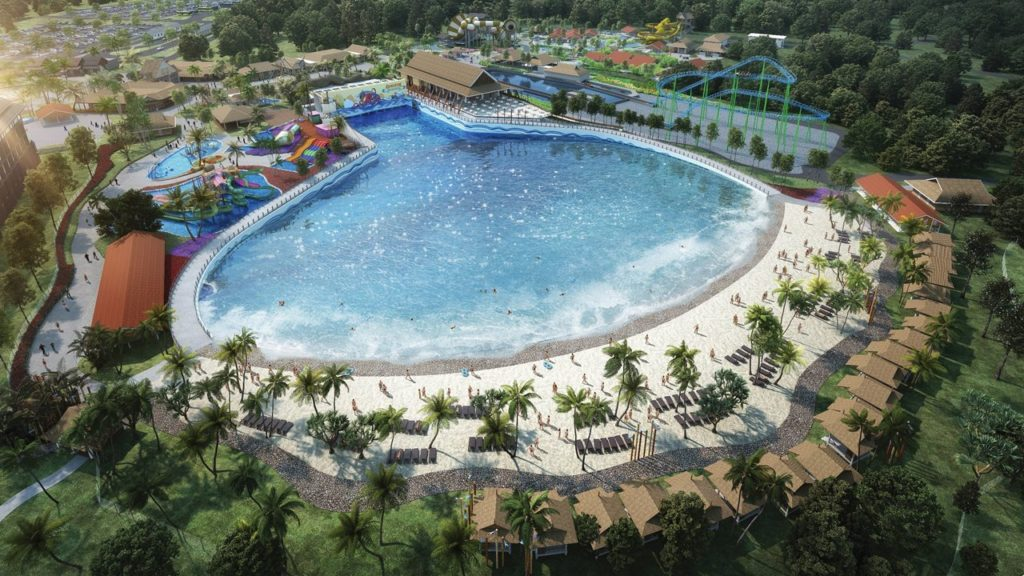 big wave pool surrounded by beach and palm trees