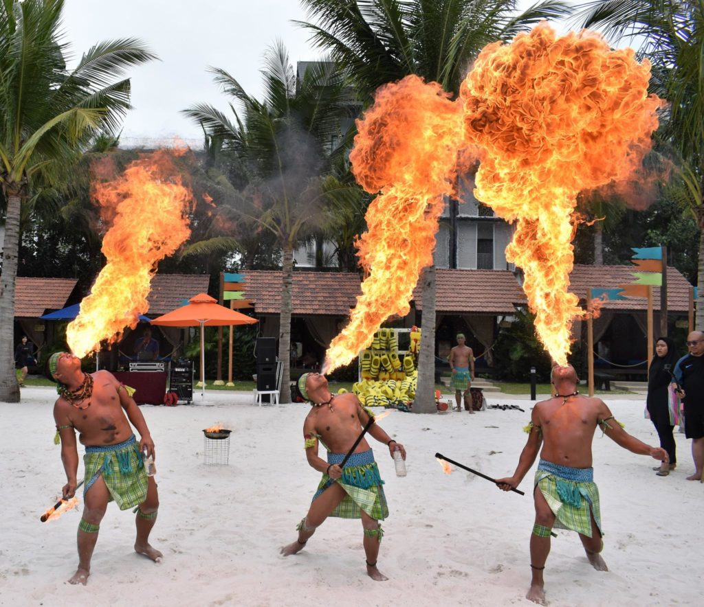 3 fire blowers performing on the beach