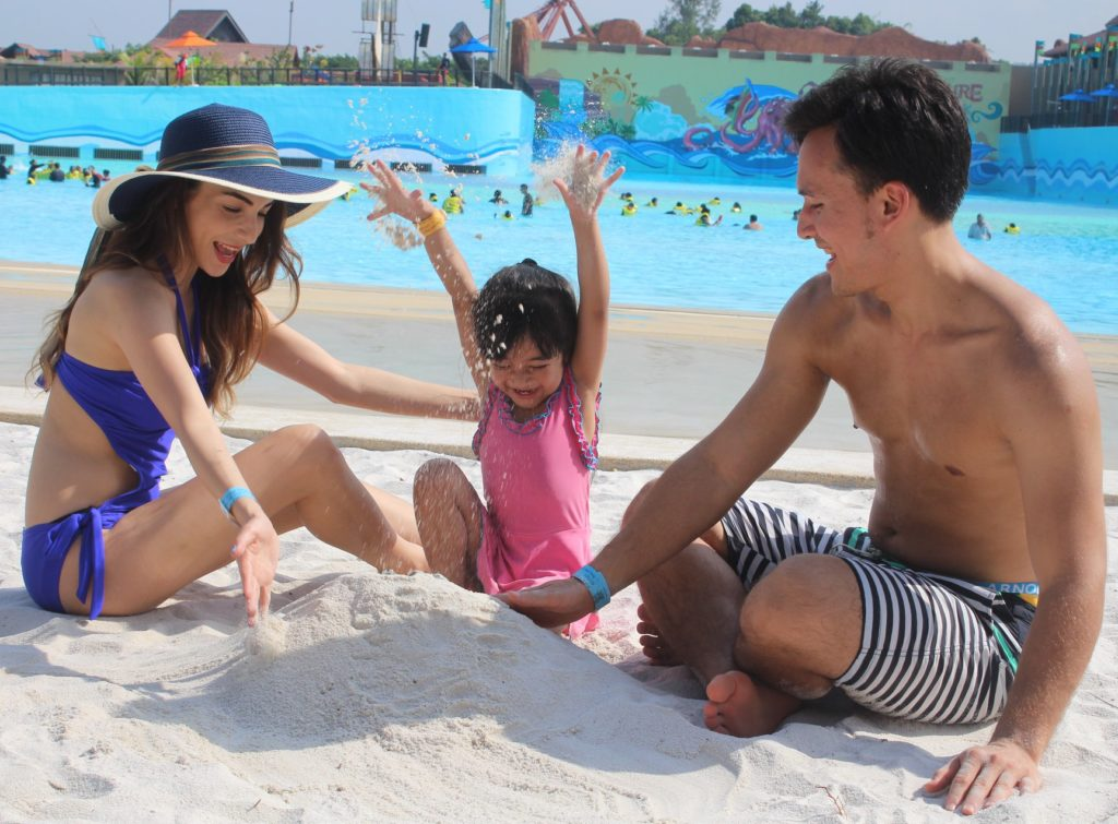 Family of 3 building sand castles by the beach