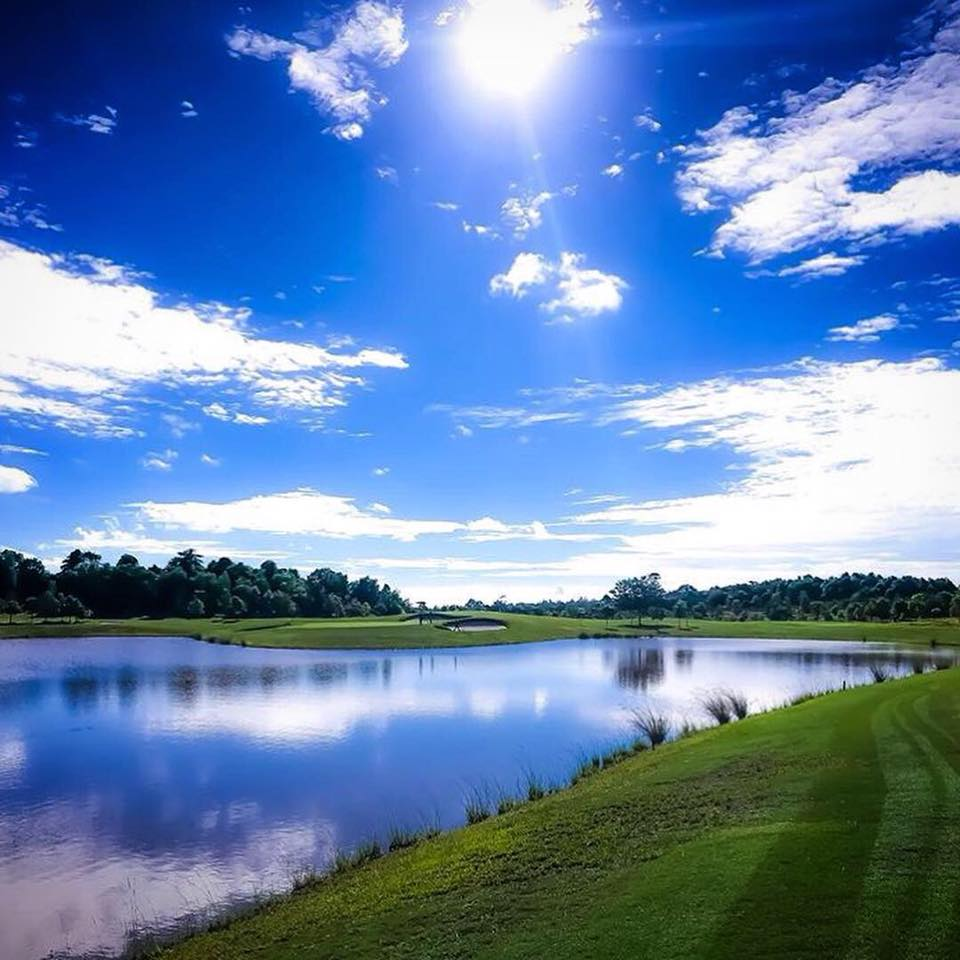 green fairways with blue skies over lake