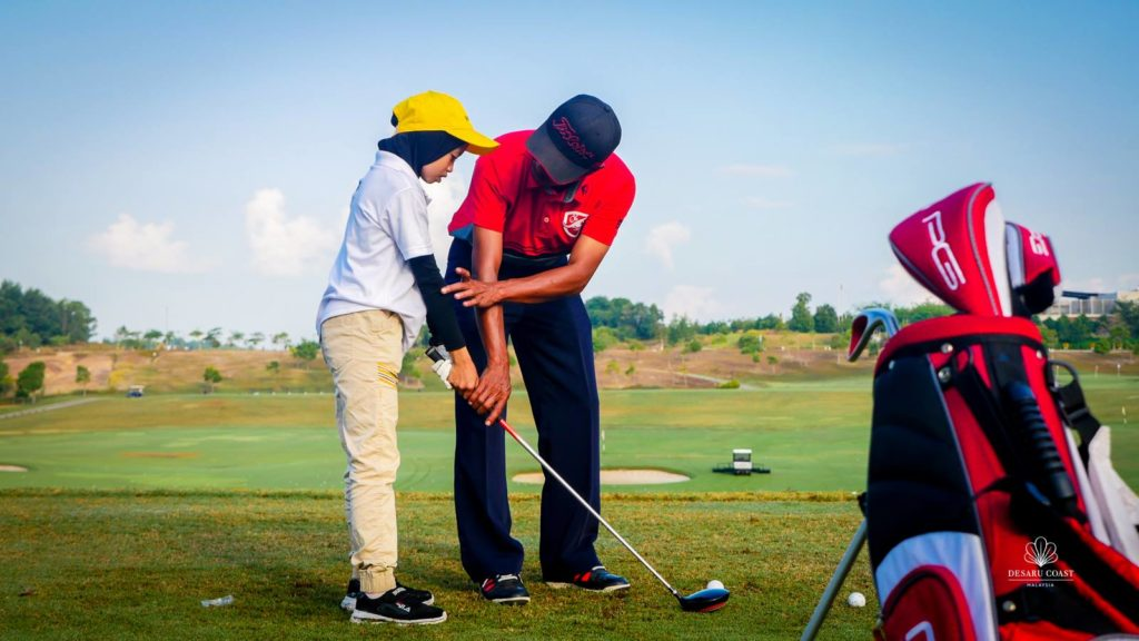 Junior golfers learning golf from coach