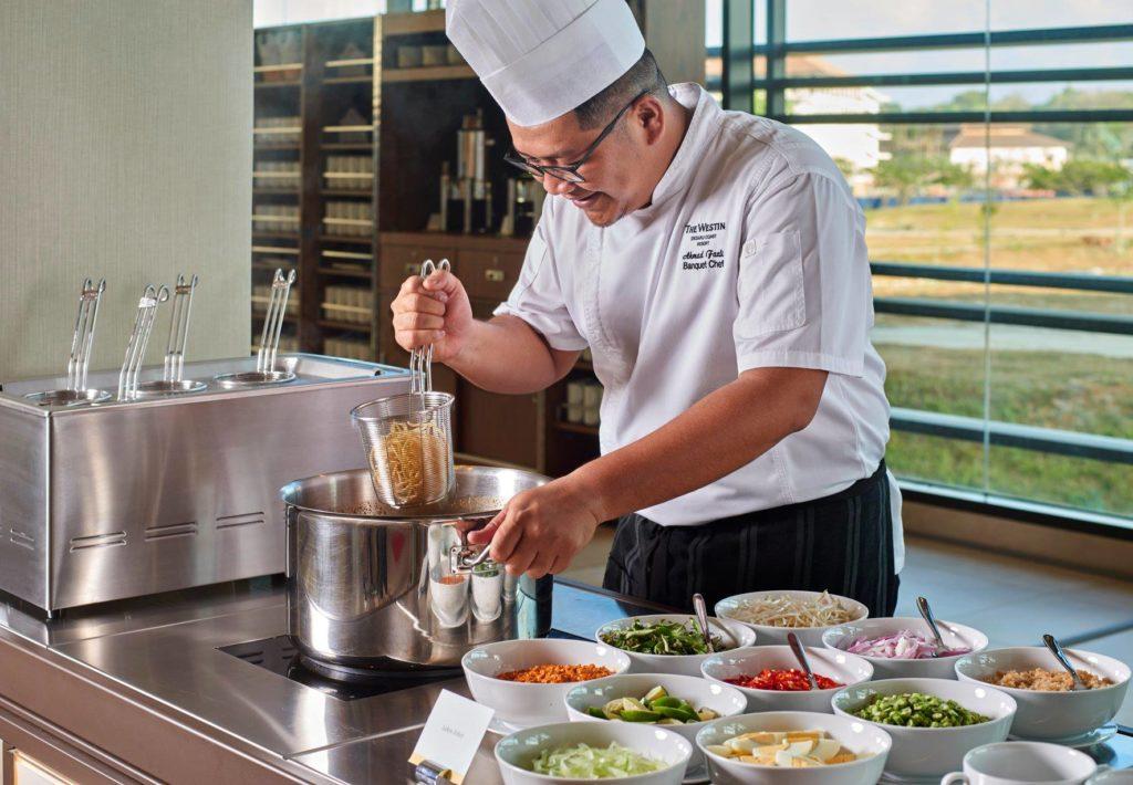 Master chef in restaurant preparing food in open kitchen