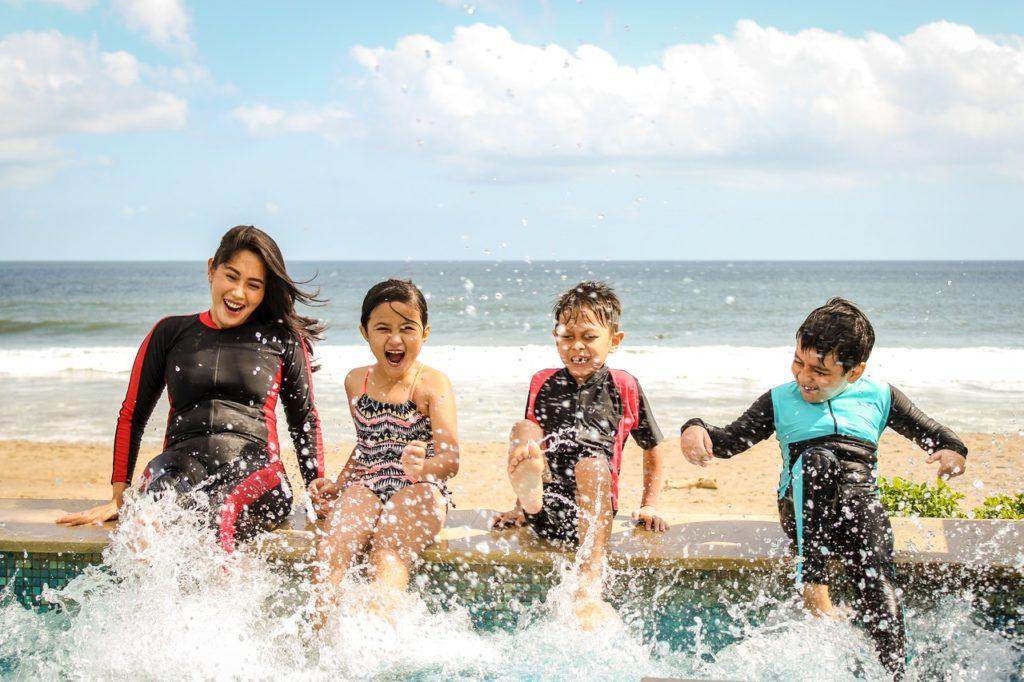 4 persons splashing by the beach in their swimwear