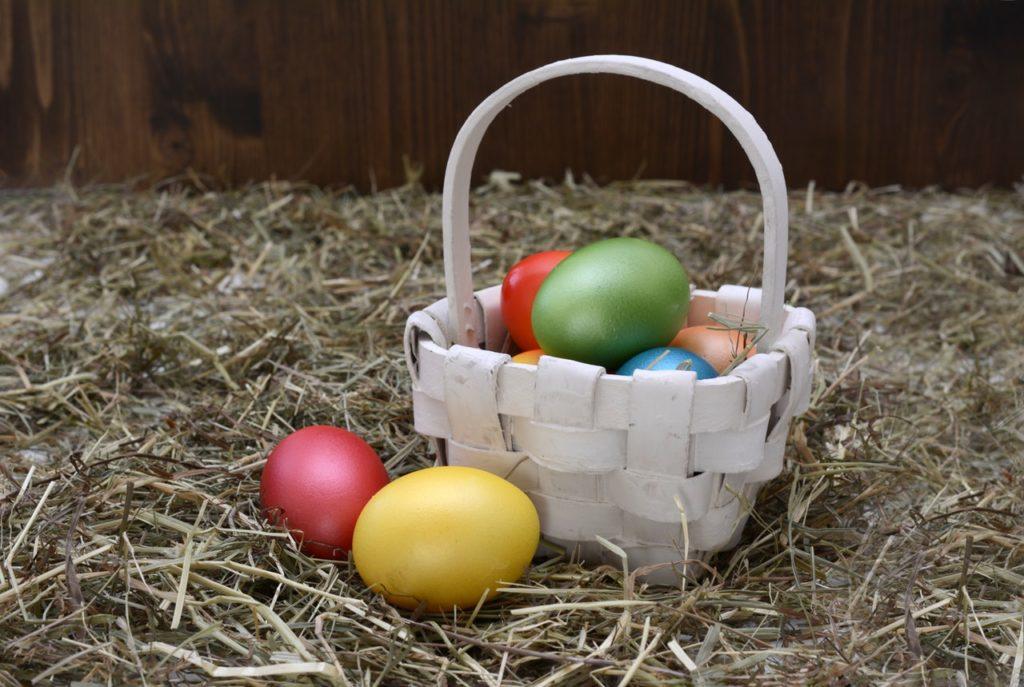 coloured eggs in white basket
