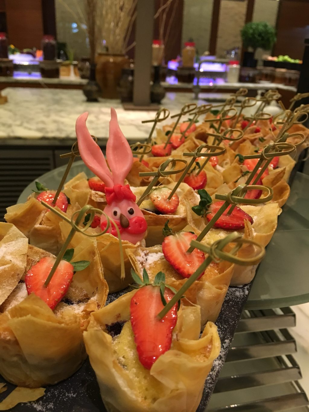 Pastries at buffet table with pink bunny at centre