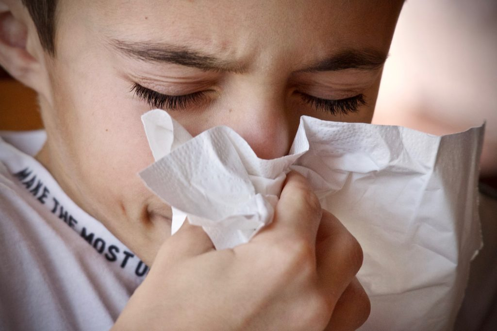 kid blowing nose into tissue