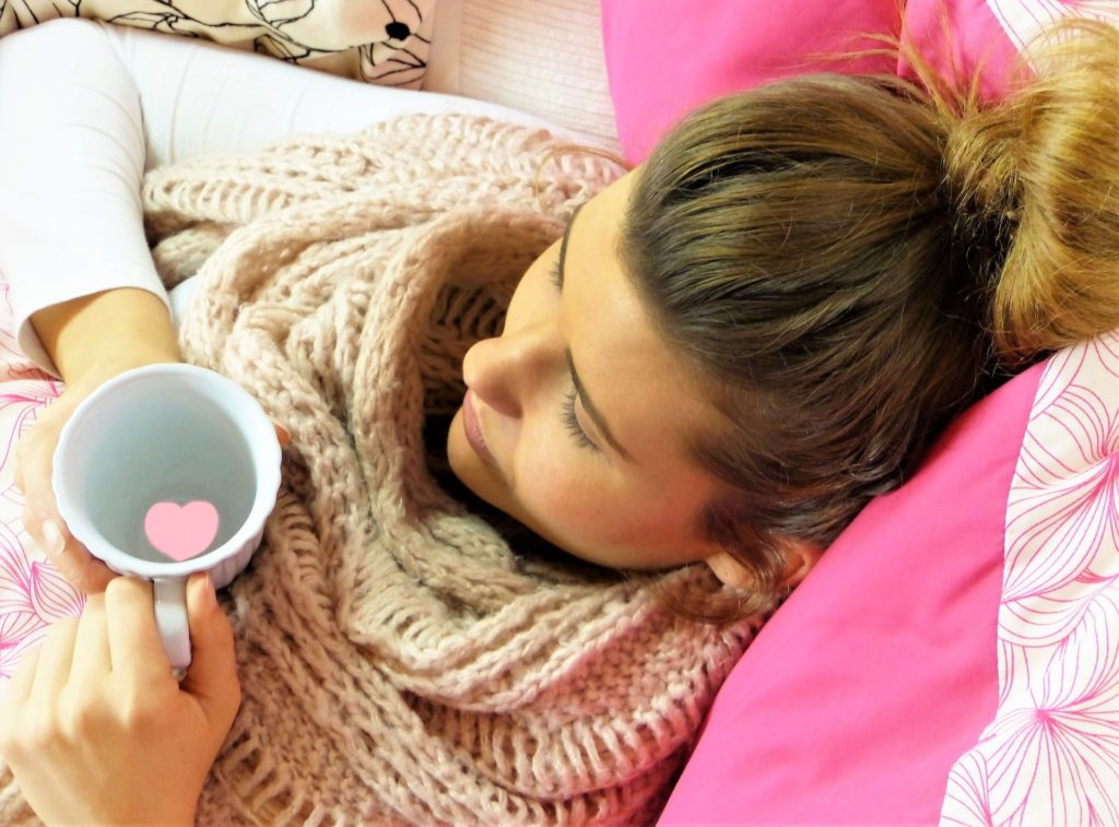 lady in bed with warm drink in hand