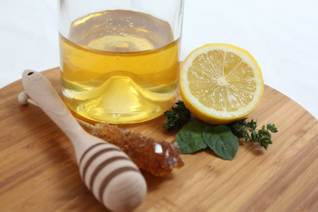 honey drink in glass with lemon on side on brown board
