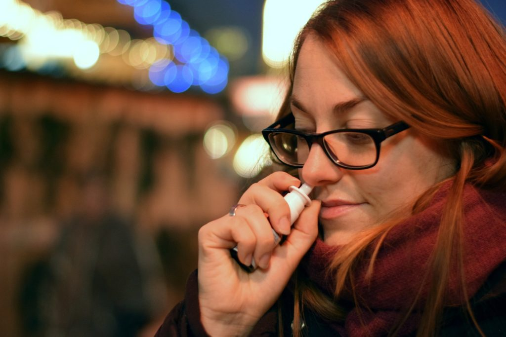 lady with spectacles using nasal spray into nose