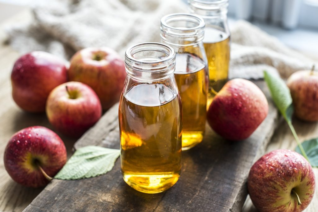 3 clear jars of apple cider vinegar with red apples around