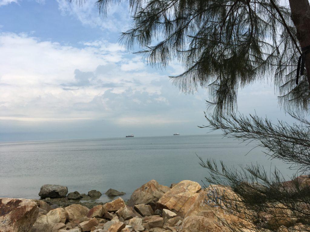 Minyak Beku beach with rocks and blue skies