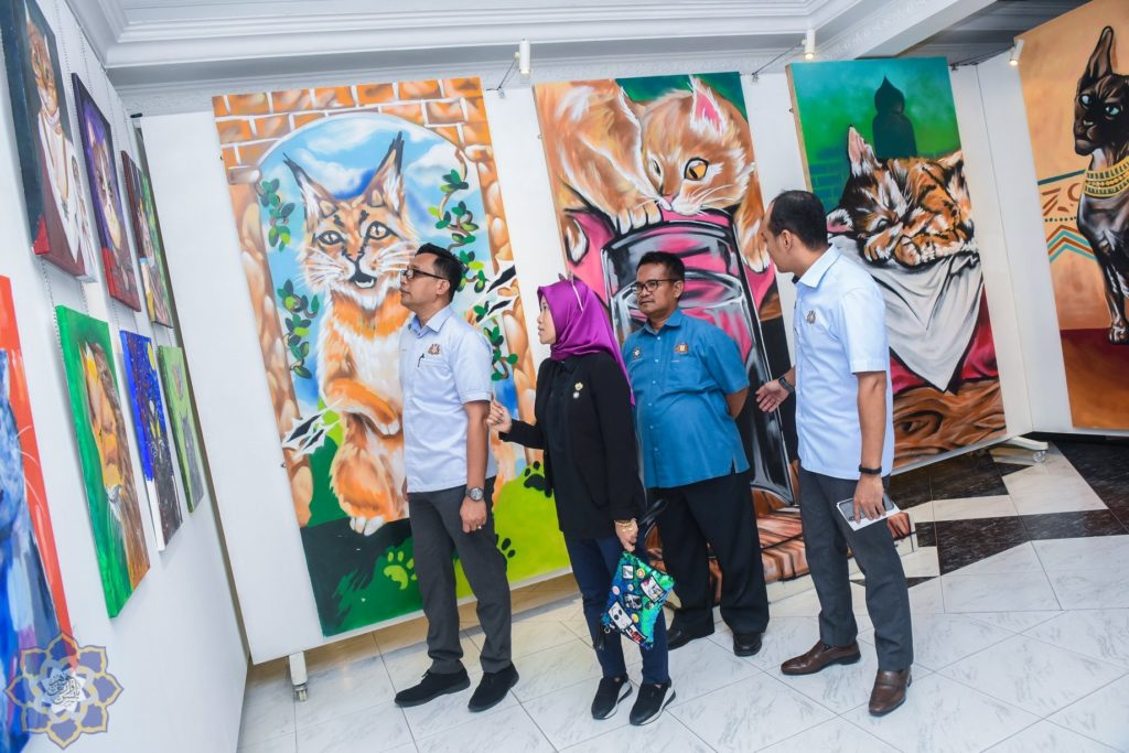 4 persons viewing art pieces of cats