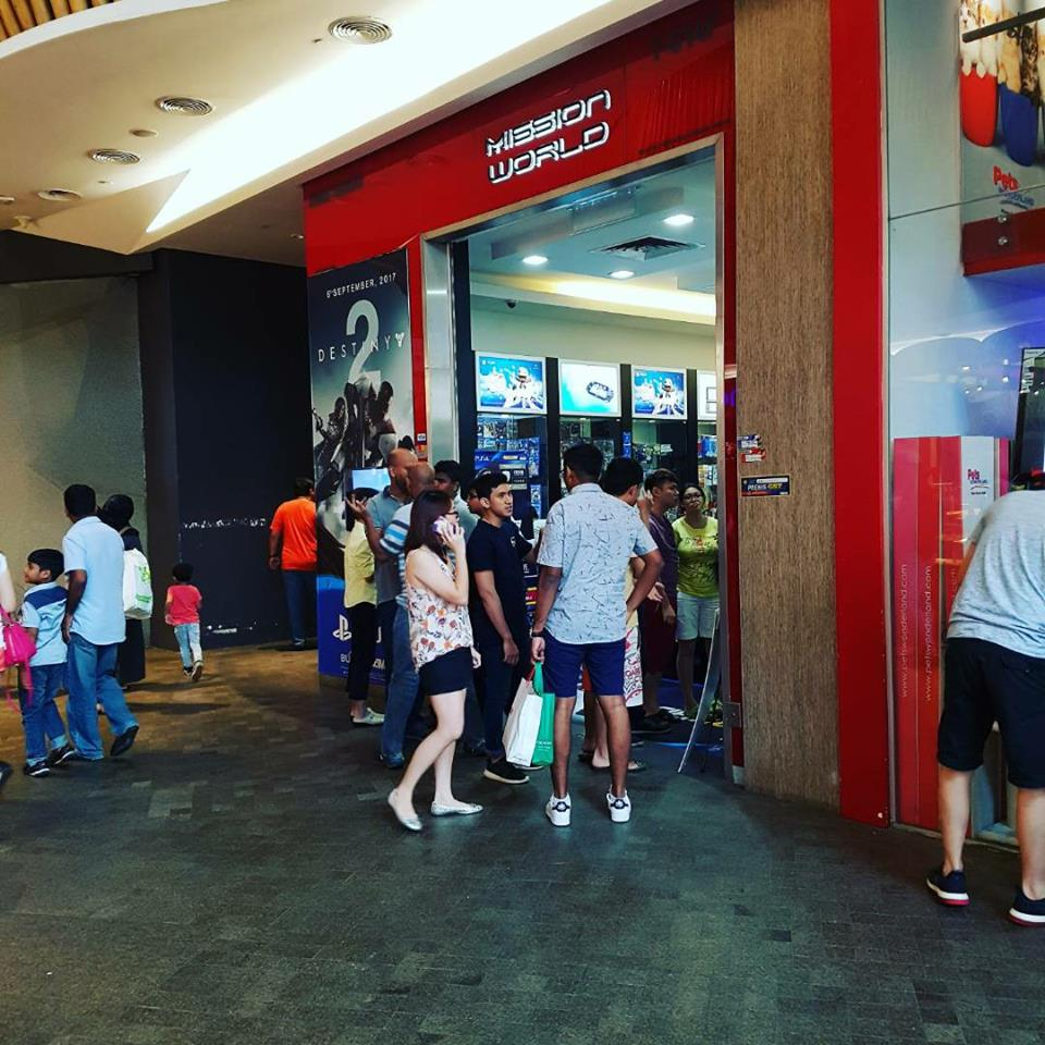 Frontage of Mission World shop with customers around