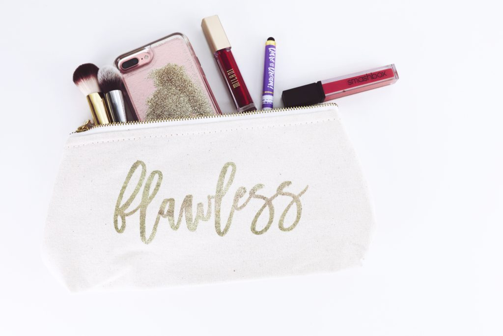 A white make up bag with contents out and with flawless on it in gold