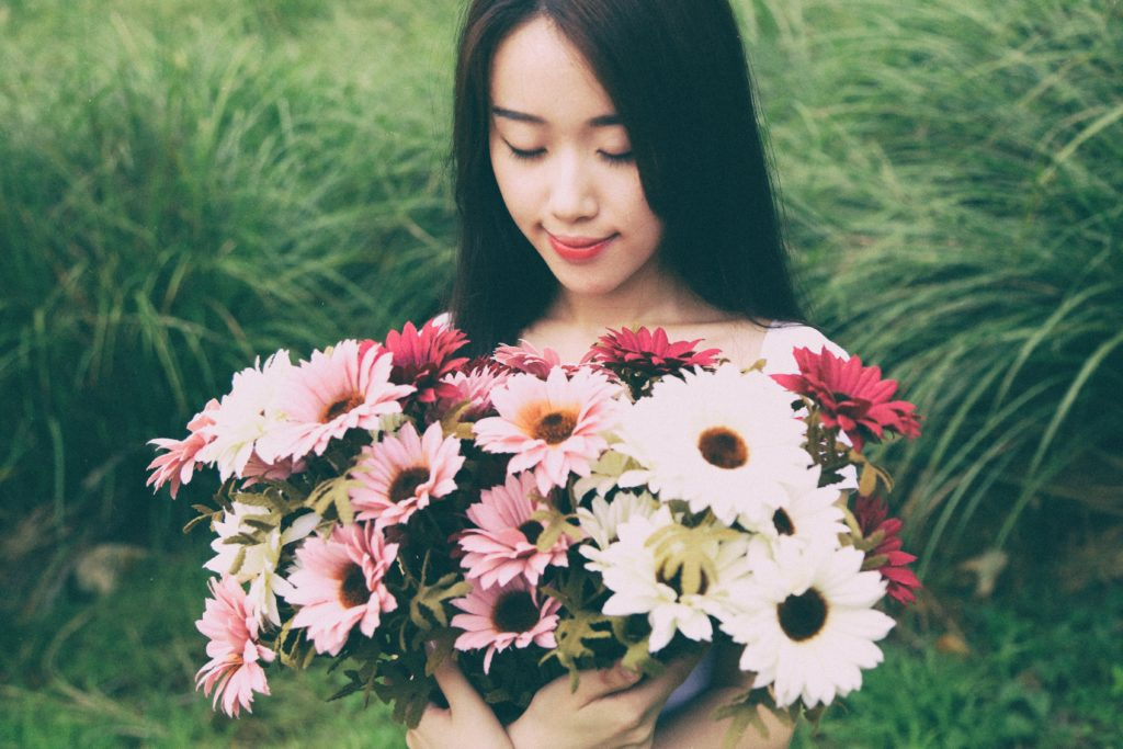 An Asian lady holding a bouquet of flowers